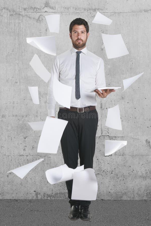 Jonge zakenman die zich met vliegende documenten bevinden. royalty-vrije stock afbeeldingen