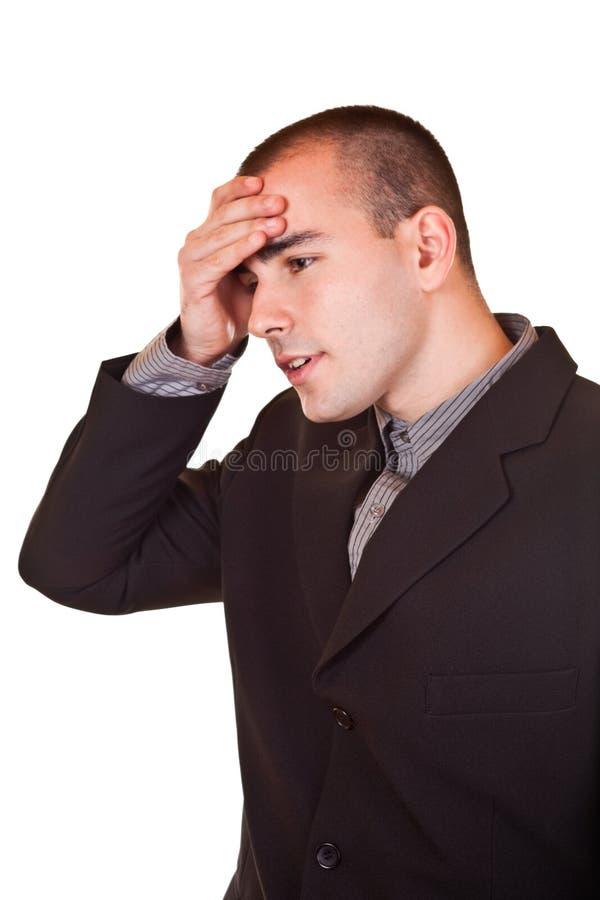Jonge zakenman die zijn hoofd houdt stock afbeelding