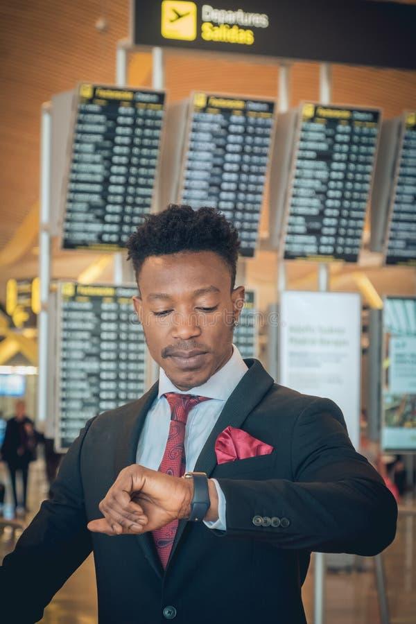 Jonge zakenman die zijn slim horloge in de luchthaven in F bekijken stock fotografie