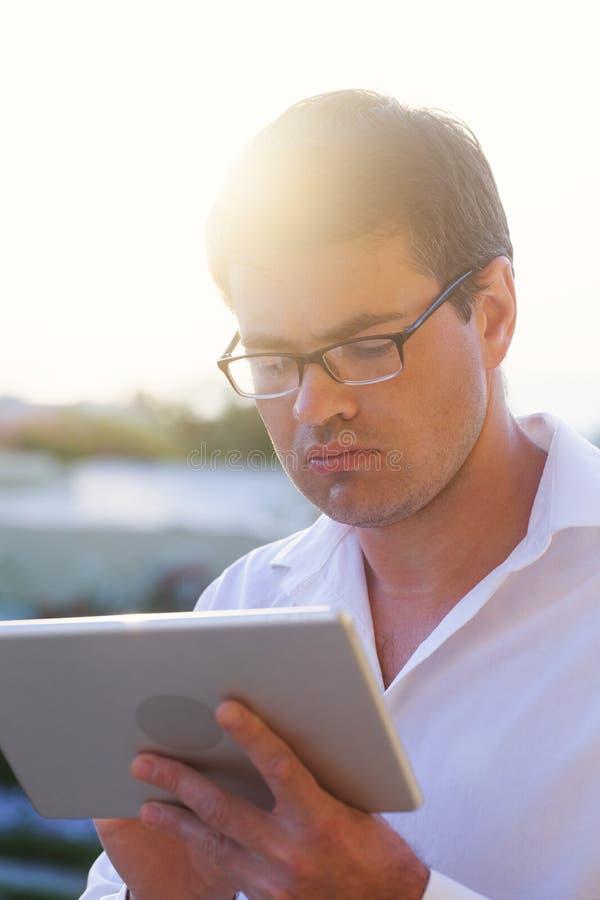 Jonge zakenman diep aan het werk met stootkussen openlucht royalty-vrije stock afbeeldingen