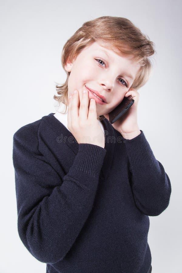 Jonge zakenman in een blauwe sweater die op de telefoon en KMIO spreken royalty-vrije stock foto's