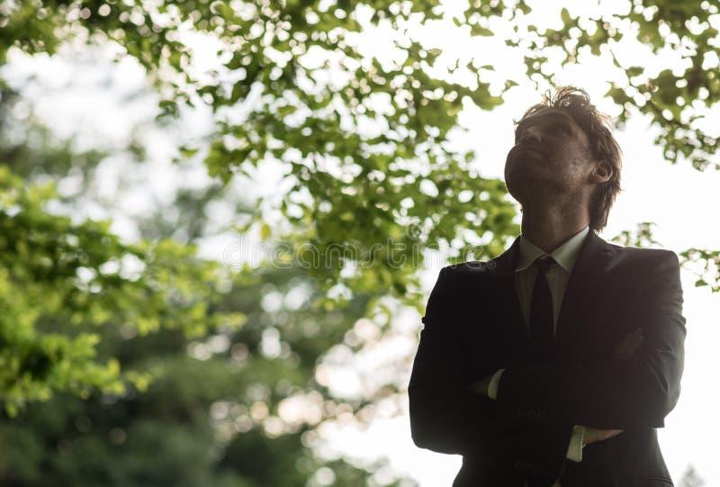 Jonge zakenman in een kostuum die zich in een groen bos bevinden stock fotografie