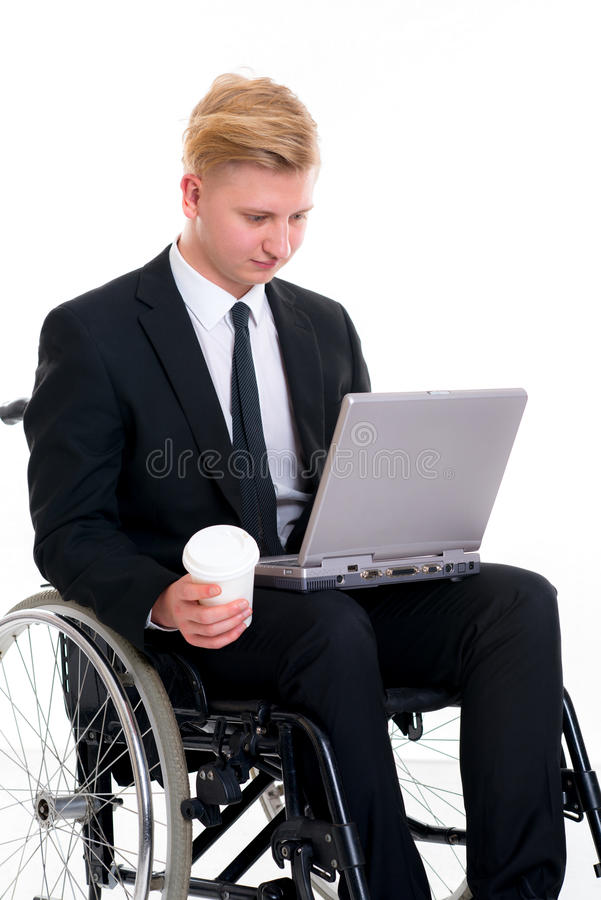 Jonge zakenman in een rolstoel met computer en koffiemok stock foto