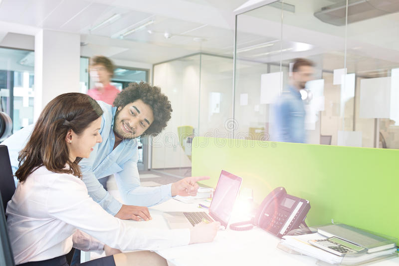 Jonge zakenman en onderneemster die over laptop in bureau bespreken stock foto's