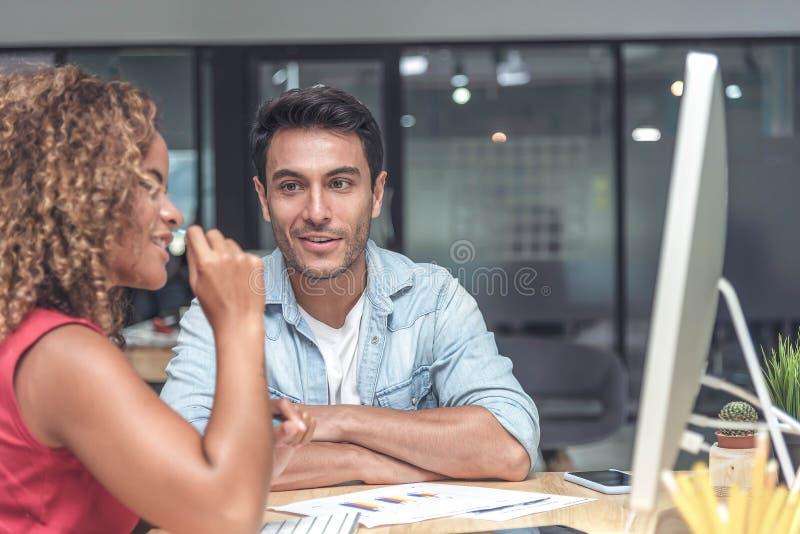 Jonge zakenman en onderneemster in vrijetijdskleding die een nieuwe projectbespreking hebben of een idee hebben op het werk stock foto