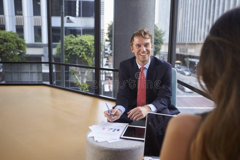 Jonge zakenman en vrouw die op een informele vergadering spreken royalty-vrije stock afbeeldingen
