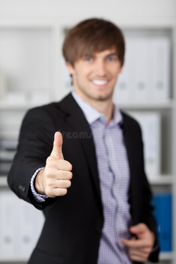 Jonge Zakenman Gesturing Thumbs Up in Bureau stock foto's