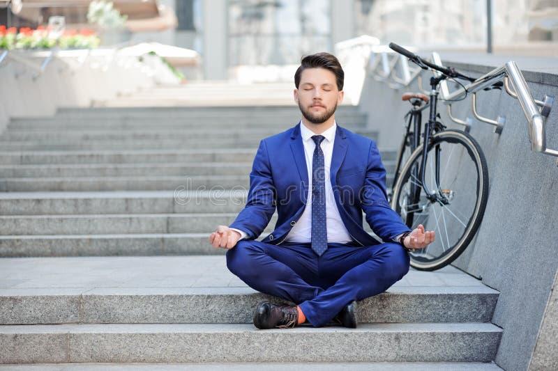 Jonge zakenman het praktizeren yoga op treden royalty-vrije stock afbeeldingen