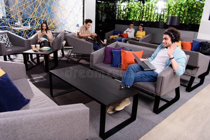 jonge zakenman in hoofdtelefoons die op laag met laptop zitten en met de hand bij het moderne coworking golven royalty-vrije stock foto
