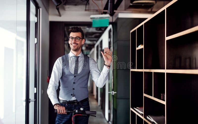 Jonge zakenman met autoped in een bureaugebouw, die bij somebody golven royalty-vrije stock foto's