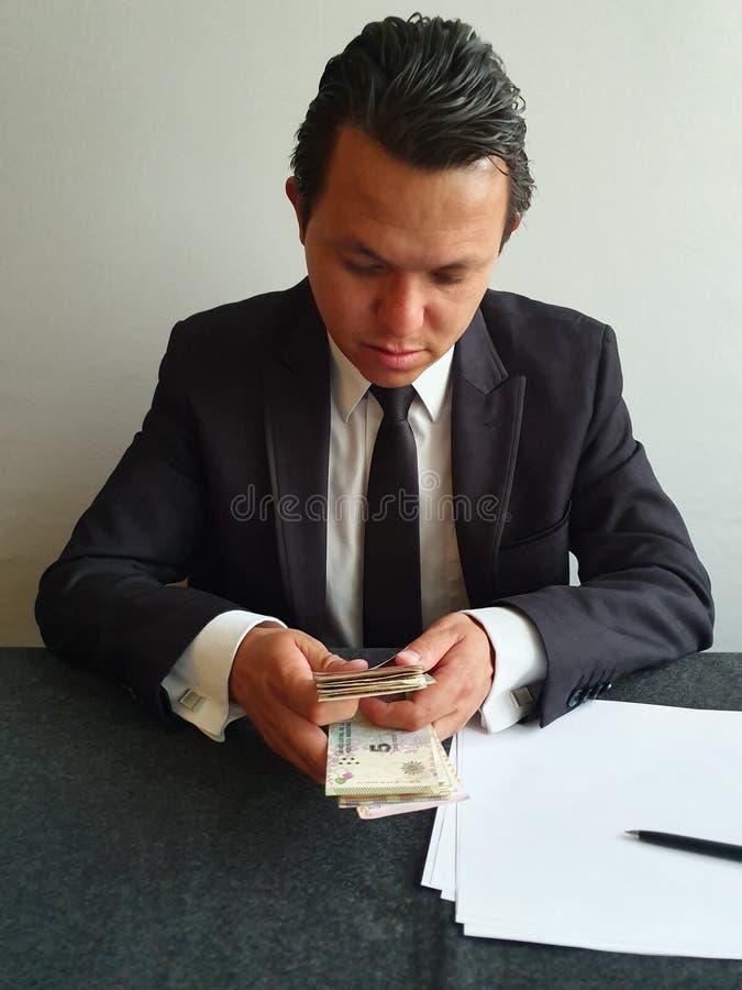 jonge zakenman met een zwart pak tellen Argentijns geld royalty-vrije stock fotografie