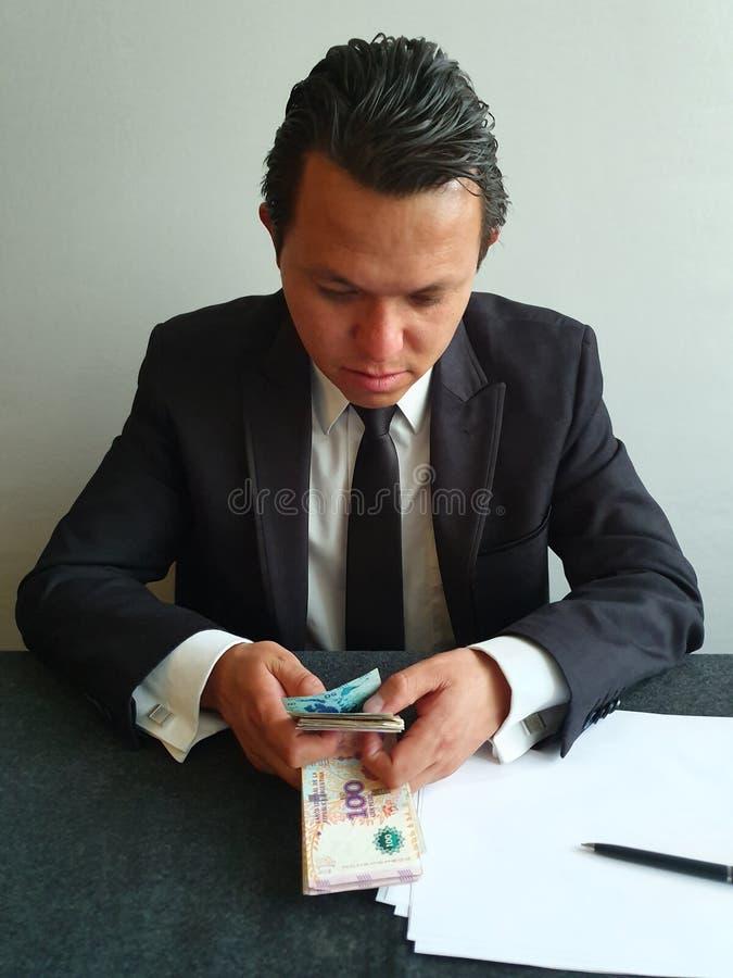 jonge zakenman met een zwart pak tellen Argentijns geld royalty-vrije stock foto