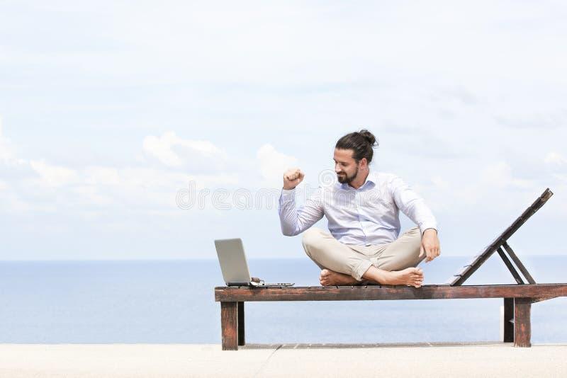 Jonge zakenman op het strand die op zijn ligstoel rusten die zijn tablet gebruiken stock fotografie