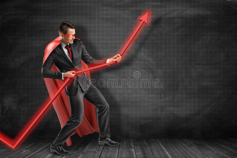 Jonge zakenman rode kaap dragen en masker die rode grafische pijl houden benadrukkend royalty-vrije stock afbeelding