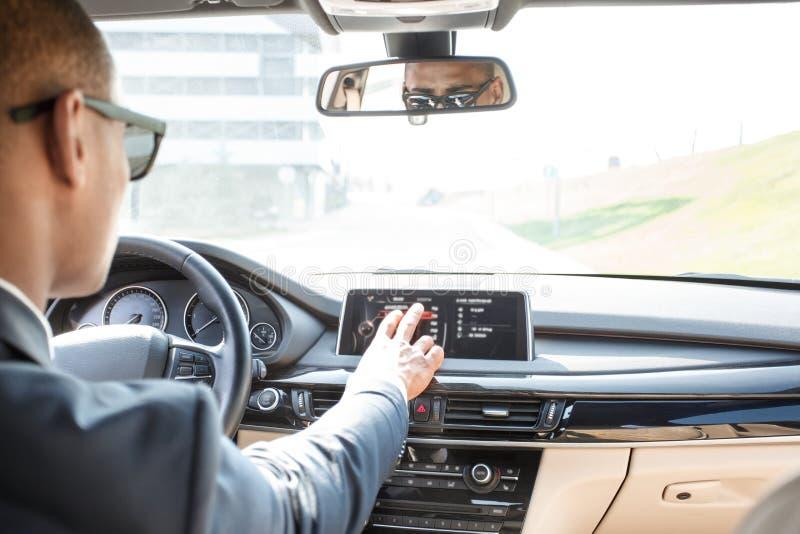 Jonge zakenmanbestuurder die in zonnebril binnen auto drijven zitten die bestemming op de mening van de navigator achterbank kiez royalty-vrije stock foto