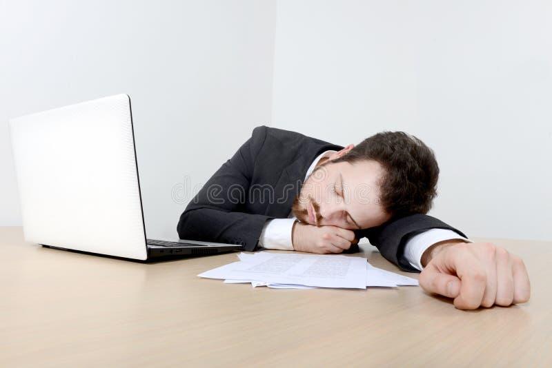Jonge zakenmanslaap op het bureau stock afbeelding