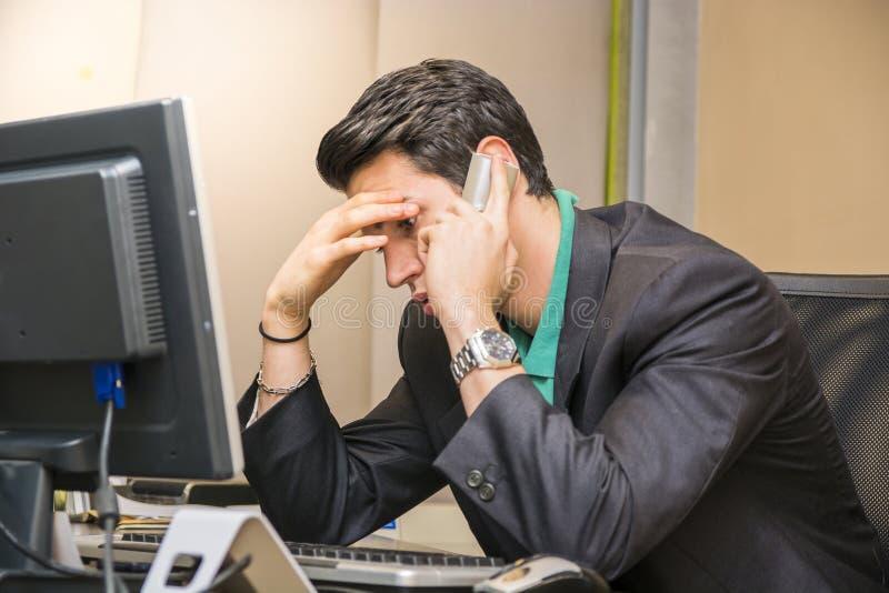 Jonge zakenmanzitting bij bureau in bureau bezig op telefoon stock afbeelding