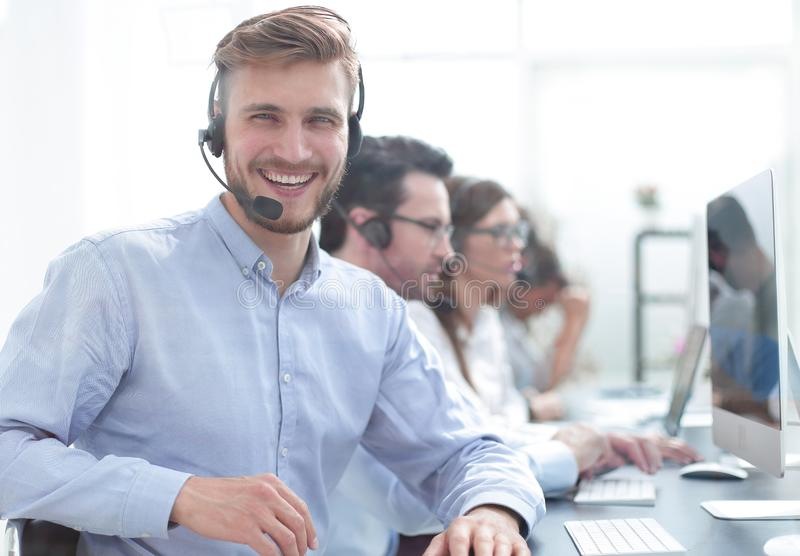Jonge zakenmanzitting bij de lijst in het call centre royalty-vrije stock foto's