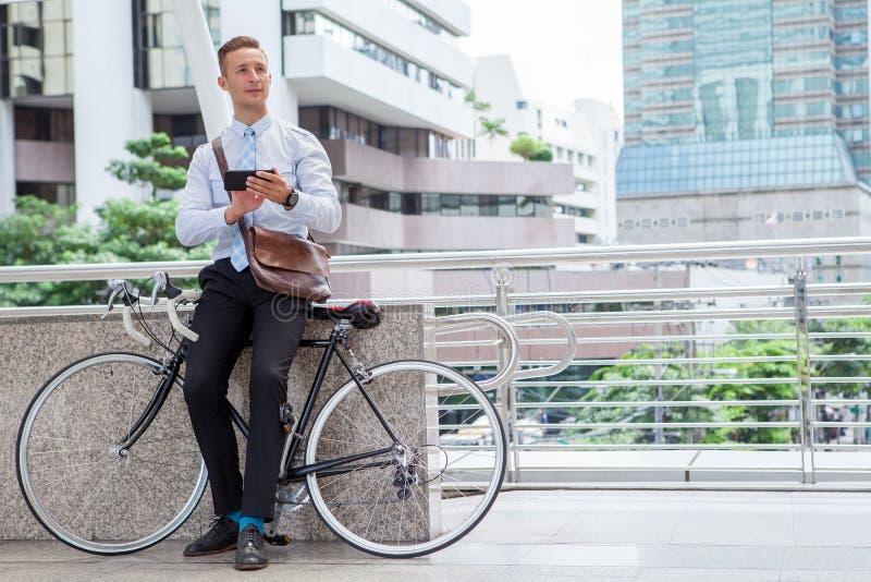 Jonge zakenmanzitting met fiets die smartphone gebruiken die een rust nemen en op straat in stedelijke stad ontspannen stock fotografie