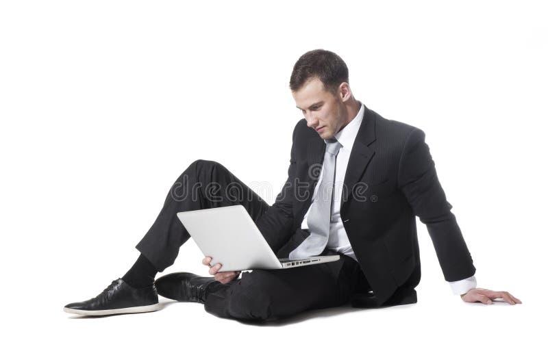 Jonge zakenmanzitting met laptop stock foto's