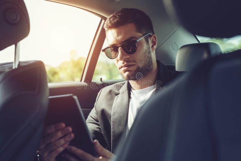 Jonge zakenmanzitting op achterbank van auto en wat betreft digitale tablet royalty-vrije stock foto's