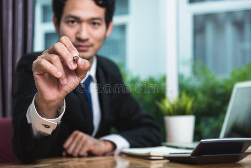 Jonge zakenmanzitting op bureautekening royalty-vrije stock afbeelding