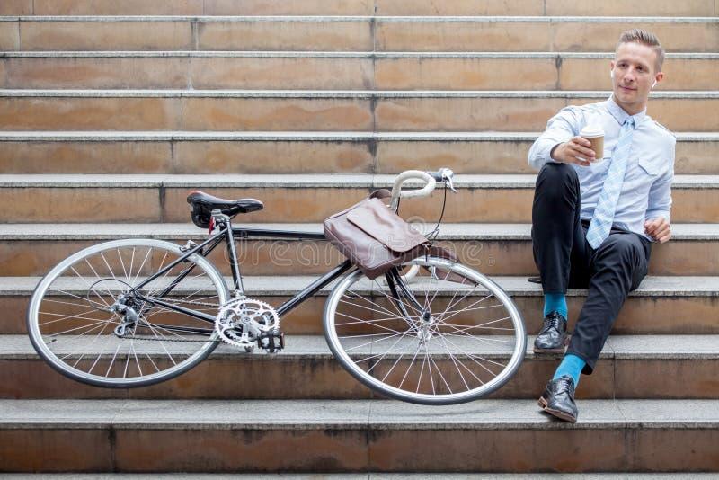 Jonge zakenmanzitting op de treden met het document van de fietsholding koffiekop die een rust nemen en op straat in stedelijke s royalty-vrije stock fotografie