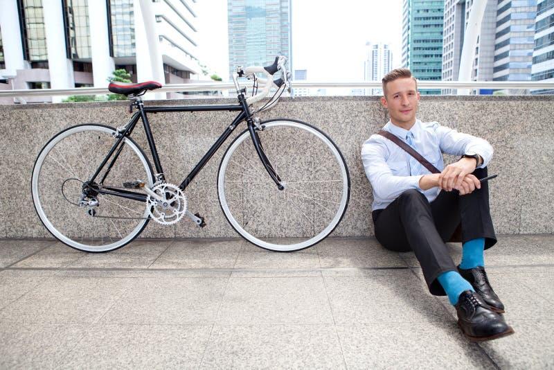 Jonge zakenmanzitting op vloer met fiets die een rust nemen en op straat in stedelijke stad ontspannen stock foto's