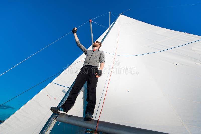 Jonge zeeman op een zeilboot die zich op een zeilboom bevinden Kapitein van het jacht in de open zee stock afbeeldingen