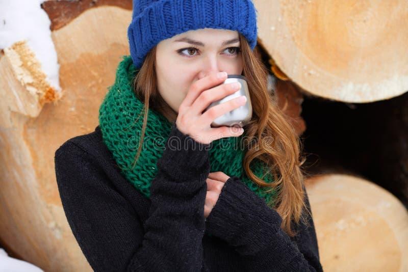 Jonge zeer positieve vrouw in sweater het blauwe grappige gebreide hoed stellen met thermosflessen in de winter bospark tegen gro stock afbeeldingen