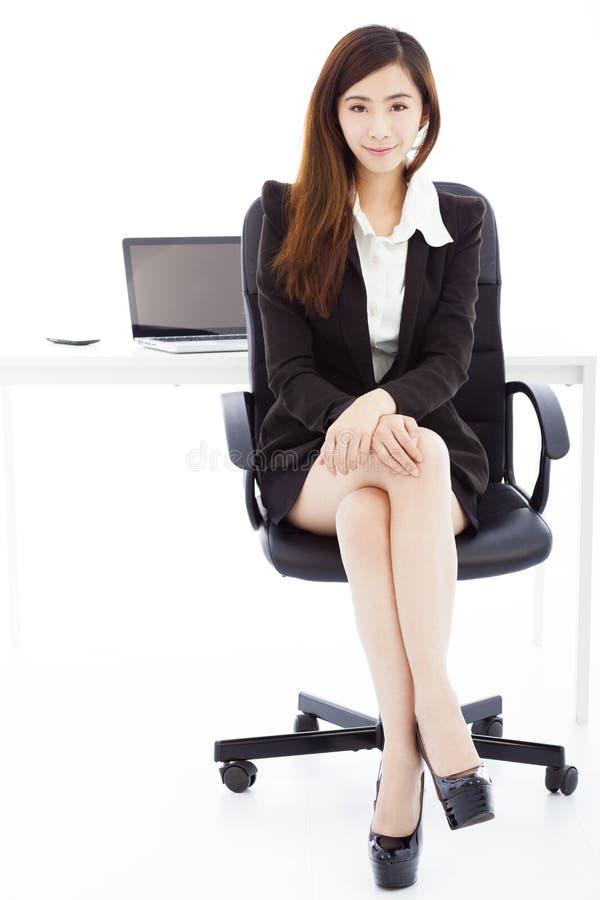 Jonge zekere bedrijfsvrouwenzitting in haar bureau stock afbeelding