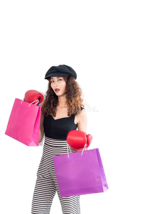 Jonge zekere gekke Aziatische vrouw die rode bokshandschoenen dragen en houdend die het winkelen zak op witte achtergrond wordt g royalty-vrije stock foto's