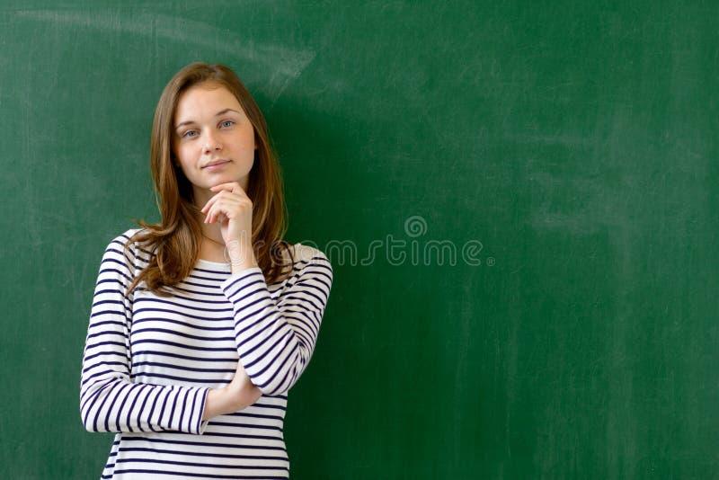 Jonge zekere glimlachende vrouwelijke middelbare schoolstudent die zich voor bord in klaslokaal bevinden stock afbeelding