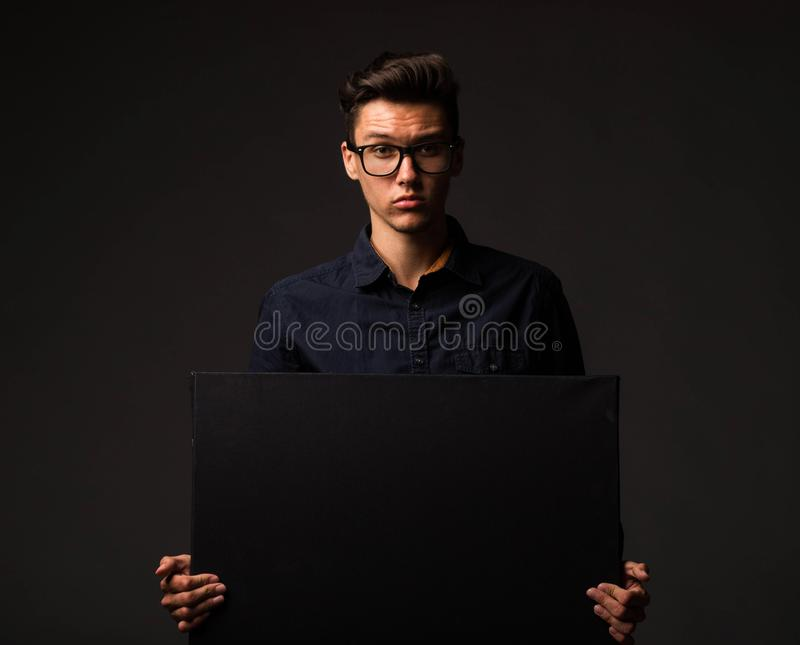 Jonge zekere mens die presentatie tonen, die op aanplakbiljet richten stock afbeeldingen