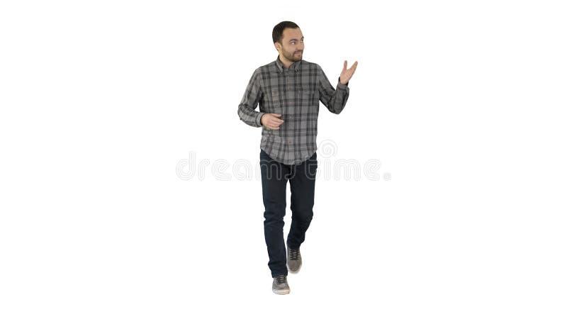 Jonge zekere mens in overhemd en jeans die naar camera lopen en aan de kanten op witte achtergrond richten royalty-vrije stock fotografie