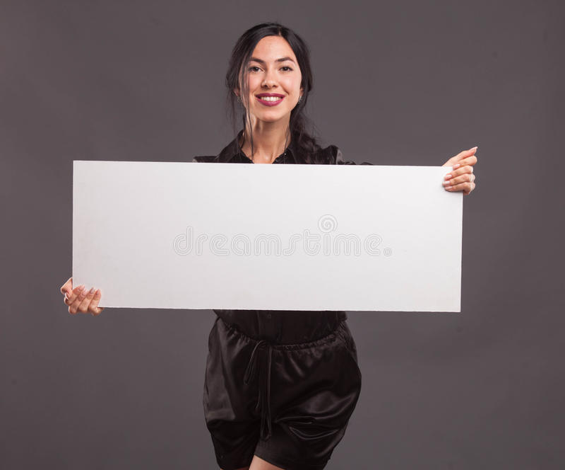 Jonge zekere vrouw die presentatie tonen, die op aanplakbiljet richten royalty-vrije stock foto