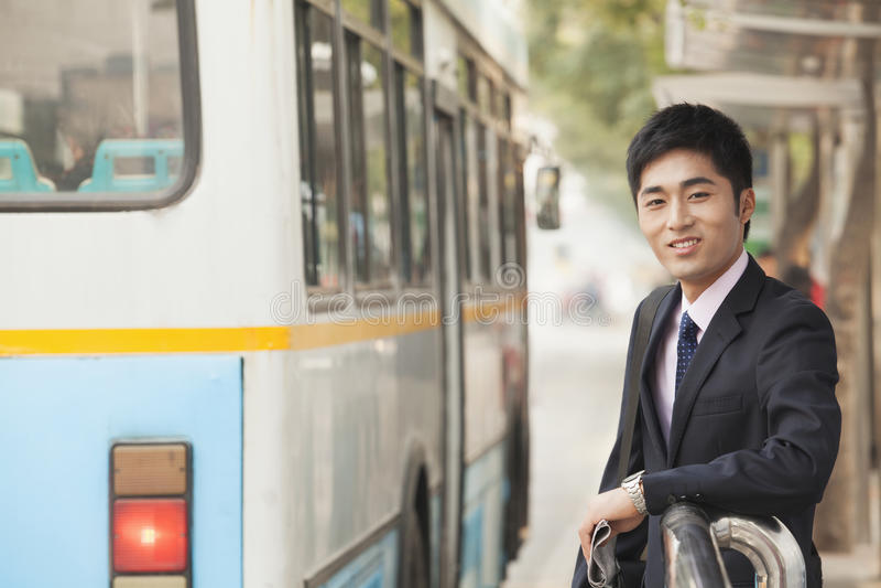 Jonge, zekere zakenman die bij de bushalte op de bus in Peking, China wachten stock afbeeldingen