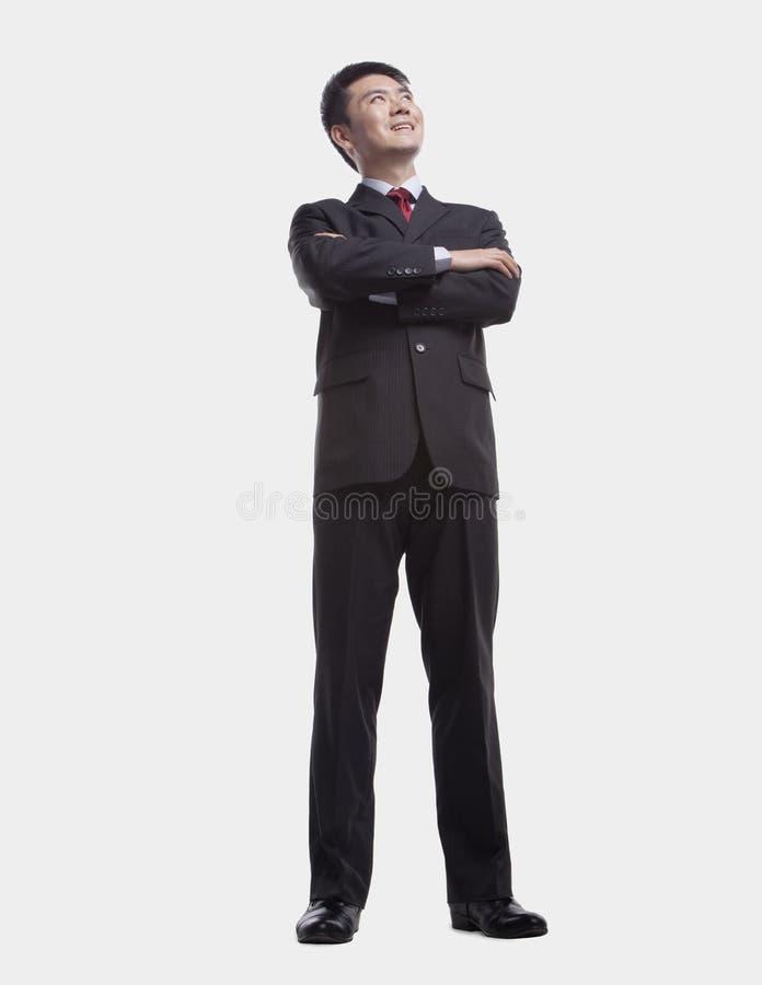 Jonge, zekere zakenman die omhoog met gekruiste wapens kijken, geschotene studio, volledige lengte stock afbeeldingen