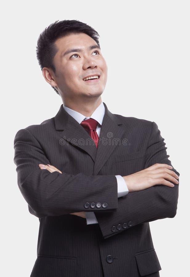 Jonge, zekere zakenman die omhoog met omhoog gekruiste wapens kijken, studioschot, taille royalty-vrije stock foto