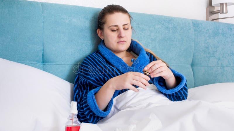 Jonge zieke vrouw die in bed en het openen fles geneeskunde liggen royalty-vrije stock fotografie