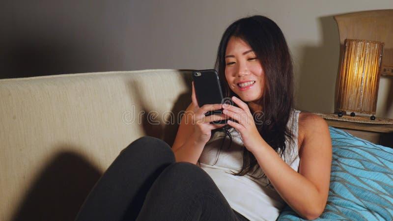 Jonge zoete gelukkige en vrij Aziatische Koreaanse vrouw die de sociale media app van Internet bij het mobiele telefoon vrolijk g royalty-vrije stock afbeelding