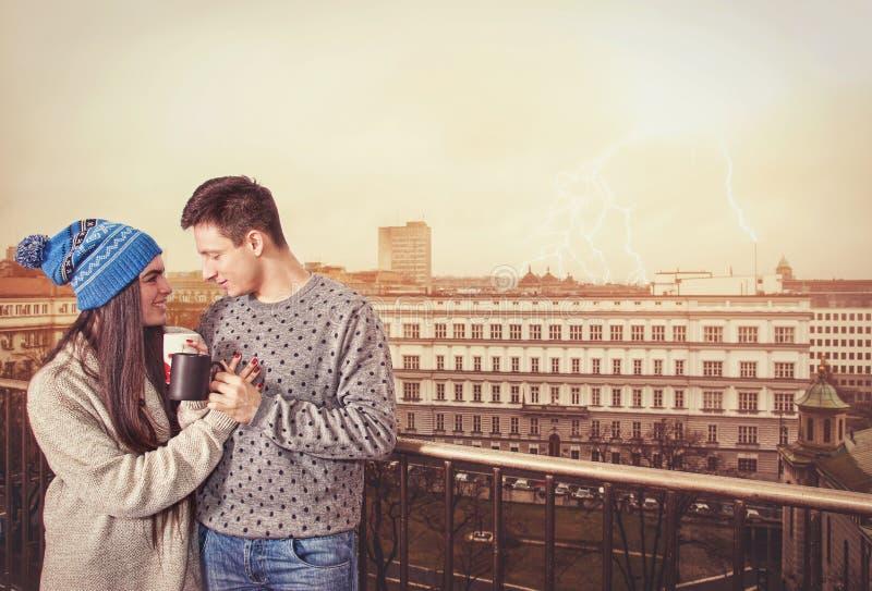 Jonge zoete romantische paar het drinken koffie die zich op terras bevinden stock foto