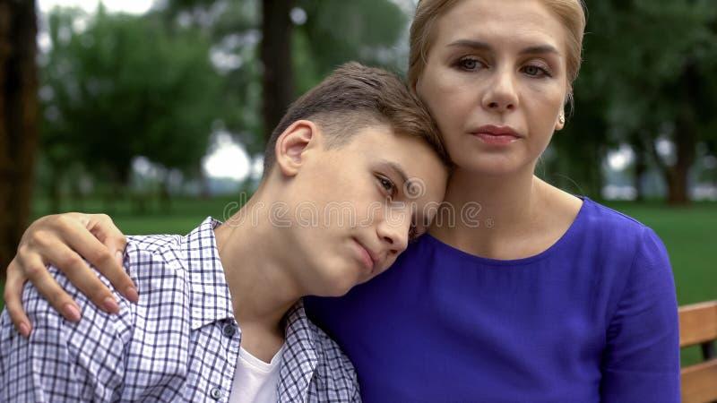 Jonge zoon die in wanhoop hoofd op moedersschouder zetten die kalmte en liefde voelen stock foto