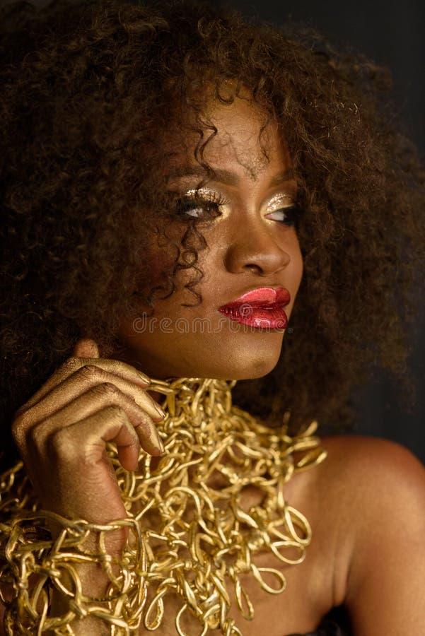 Jonge Zuidafrikaanse vrouw in gouden make-up en toebehoren met peinzend, maar sluwe uitdrukking stock afbeelding