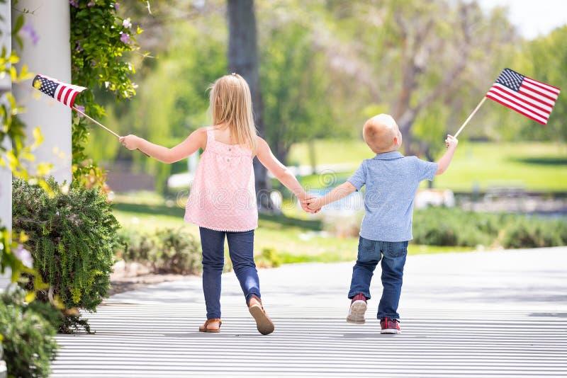 Jonge Zuster en Broer Holding Hands en Golvende Amerikaanse Vlaggen royalty-vrije stock afbeeldingen