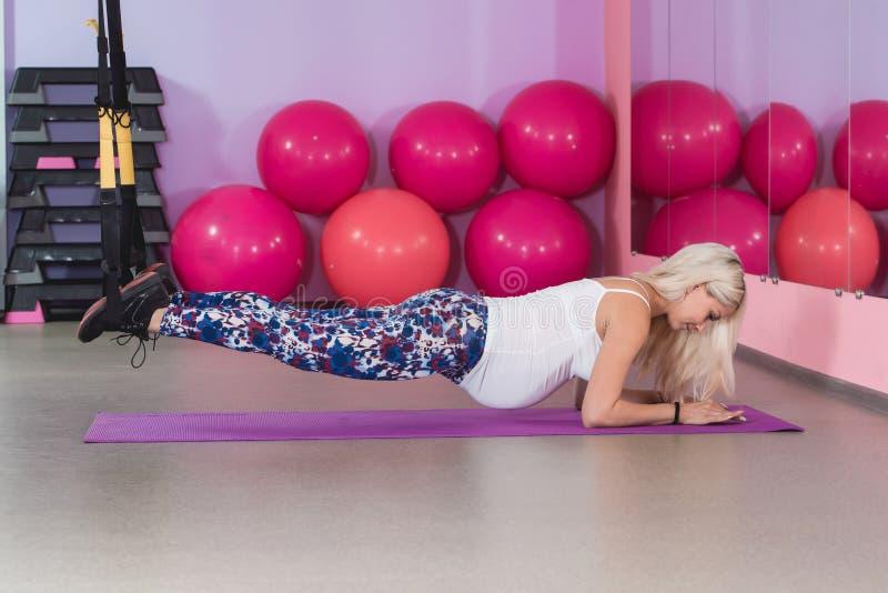 Jonge zwangere aantrekkelijke vrouw opleiding met de riemen van de trxgeschiktheid in de gymnastiek` s studio stock foto