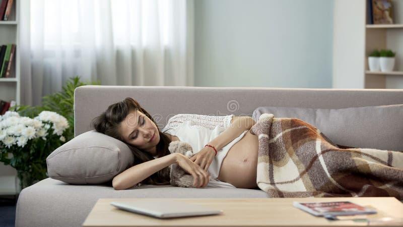 Jonge zwangere dame die rust op laag hebben, die teddybeer, moederschapszorg koesteren royalty-vrije stock afbeelding
