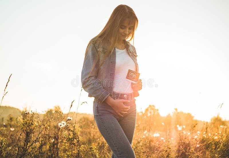 Jonge Zwangere de ultrasone klankfoto van de Vrouwenholding bij Zonsondergang en het Omhelzen van haar Buik 4 maandzwangerschap J royalty-vrije stock afbeeldingen