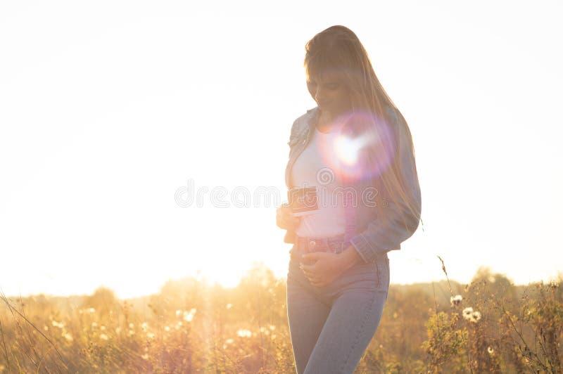 Jonge Zwangere de ultrasone klankfoto van de Vrouwenholding bij Zonsondergang en het Omhelzen van haar Buik 4 maandzwangerschap J stock afbeelding