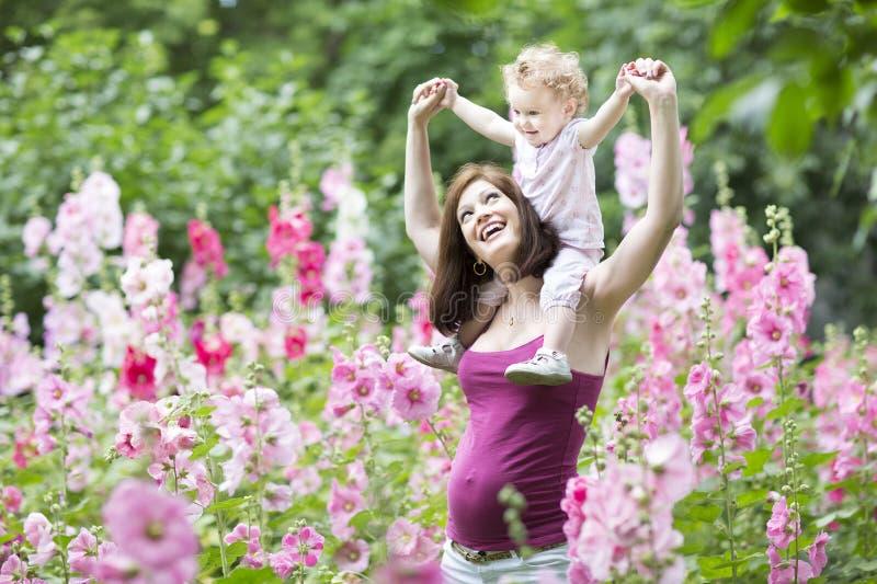 Jonge zwangere moeder met babydochter in bloemen royalty-vrije stock foto